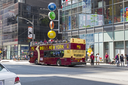 NEW YORK CITY - AUGUST 20, 2017: New York, Manhattan. Sightseeing bus under the advertising signboard of M&Ms chocolate. Editorial