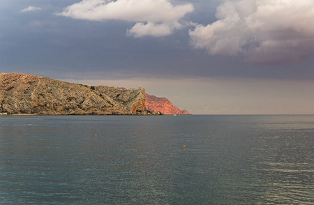 Cape Alchak and Meganom lit by the evening sun. View from the embankment of the resort town of Sudak, Crimea.