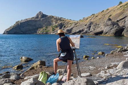 NOVYY SVET, CRIMEA - SEPTEMBER 2, 2017: The artist in the open-air. Sunny summer morning. Little bay in the Crimea. 新聞圖片