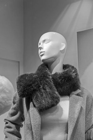 PARIS, FRANCE - DECEMBER 11, 2017: Showcase of an expensive clothing store. A dummy with a fur boa. Paris, France. Black and white version.