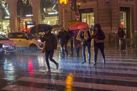 PARIS, FRANCE - DECEMBER 10, 2017: People cross the street in the pouring rain. Paris, Boulevard Haussmann, December evening.