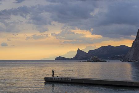 A lone fisherman on a breakwater. Evening in the Sudak bay, Crimea. Stock Photo