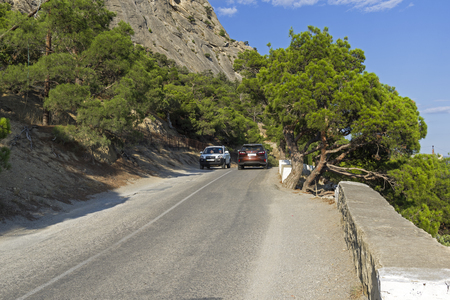 NOVYY SVET, CRIMEA - SEPTEMBER 7, 2017: Cars on a narrow mountain road. Sunny summer day. (The road Sudak - Novyy Svet, Crimea).