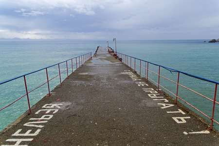 View from an empty pier towards the sea. Crimea, spring, early April. Cloudy. Translation of the words on the pier: Do not jump from the pier!.