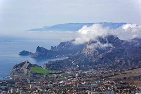The tops of the mountains are covered with clouds. View from the top of Mount Ai-George (the western extremity of the Tokluk-Syrt Range). Crimea, beginning of April. Stock Photo