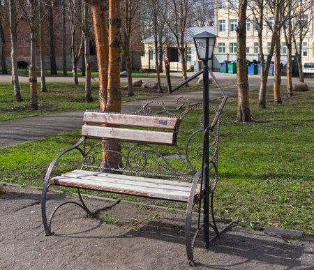 SMOLENSK, RUSSIA - APRIL 22, 2018: An amusing park sculpture is a lantern in the form of an elderly man reading a book. Lopatinsky, garden, Smolensk, Russia. End of April.