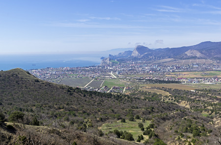 View from the slope of Mount Ai-George (the western extremity of the Tokluk-Syrt Range) to the Sudak Valley and the city of Sudak. Crimea, beginning of April. Stock Photo