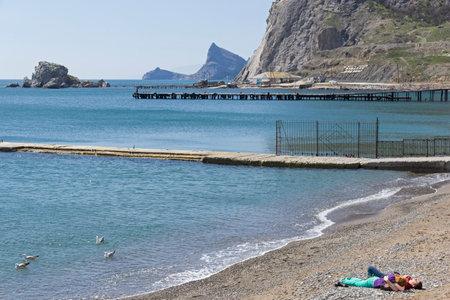 SUDAK, CRIMEA - APRIL 7, 2018: Off-season. Man and woman on an empty beach. Sudak bay,  Crimea, beginning of April.