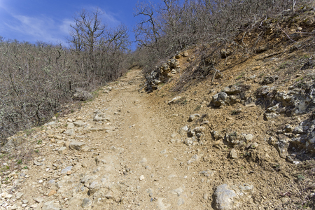 A dirt road on a steep slope. The foot of the Tokluk-Syrt mountain ridge. Crimea, spring, early April, a sunny day.