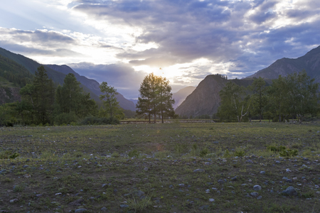 Sunset in the mountains. The shore of the Chuya River, near the village of Chibit. Altai Mountains, Siberia, Russia. August.