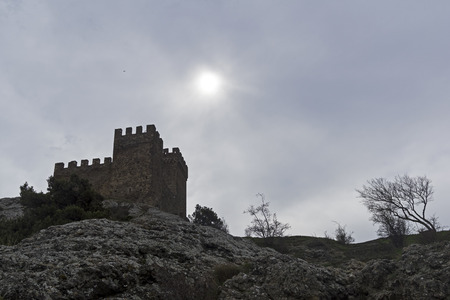 Genoese fortress in Sudak, Crimea. Consular castle and a lonely tree against a cloudy sky. Early April.