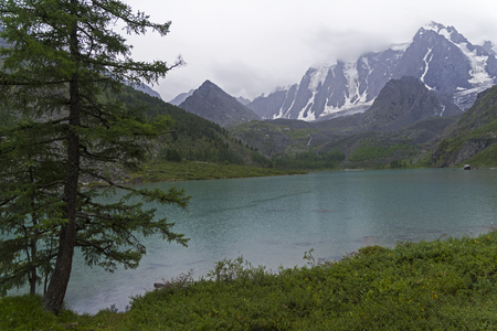 Upper Shavlinskoe Lake on a rainy day. August. Altai Mountains, Siberia, Russia.