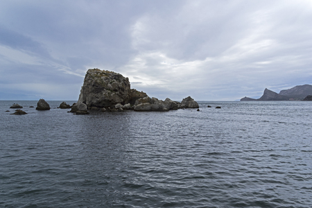 A small rocky island. Crimea, cloudy day in September.
