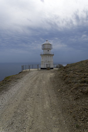 Lighthouse against the cloudy sky. Cape Meganom, Crimea, the end of September.