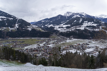 View from the mountainside to the ski resort of Zell am Ziller, Tyrol, Austria. Cloudy day in March.