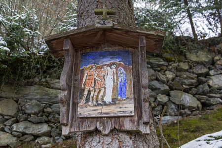 A primitivism-style icon (or picture on a biblical theme) on a tree by a forest trail on a mountainside. Zillertal valley, Tyrol, Austria.