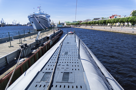 Saint Petersburg, Russia - June 16, 2019: The deck of the museum old soviet submarine against the background of a modern tourist ship.