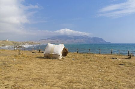Old-fashioned canvas tourist tent on a deserted seashore. Kapsel bay, Crimea, September.