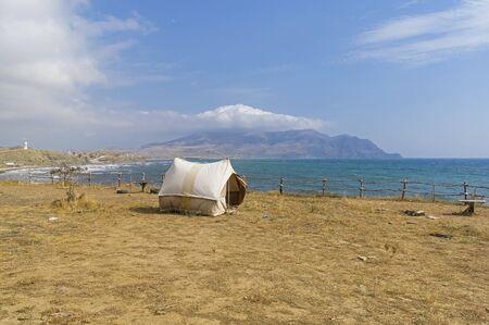 Old-fashioned canvas tourist tent on a deserted seashore. Kapsel bay, Crimea, September.