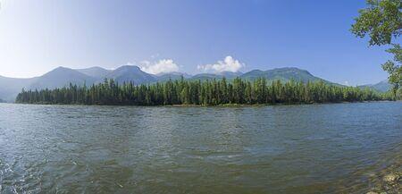 Panorama of the river bank with alps above the coastal forest. The Oka Sayan river, Orkho-Bom gorge, East Sayan, Buryatia, Siberia, Russia.