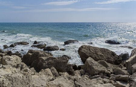 Strong surf on the rocky seashore. Crimea, a sunny day in September.