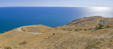 Panorama of a mountainside on the seashore with a winding dirt road going down to the lighthouse. Cape Meganom, Crimea, a sunny day in September. 版權商用圖片