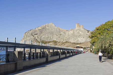 Sudak, Crimea - September 13, 2019: View from the embankment of the resort town of Sudak to the consular castle of a medieval Genoese fortress on top of a coastal mountain. Sunny day in September.. 新聞圖片