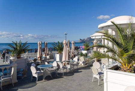 Sudak, Crimea - September 23, 2019: An empty cafe on the seaside promenade of the resort town in the early sunny morning. September. 新聞圖片