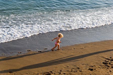 Sudak, Crimea - September 13, 2019: A small child runs along the edge of the surf on a sandy beach.