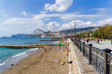 Sudak, Crimea - September 24, 2019: The promenade and the beach in the resort town of Sudak. Sunny day in September.