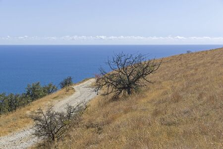 A dirt road running along a deserted mountainside on the seashore. Cape Meganom, Crimea, a sunny day in September.