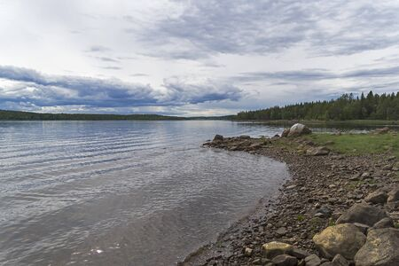 The shore of the White Sea. The littoral zone is almost completely flooded with water. Kandalaksha Gulf, Karelia, Russia, end of June.