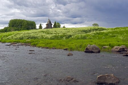 Wooden chapel on the banks of the river Keret. At this point the Keret River flows into the White Sea. Karelia, Russia, end of June.