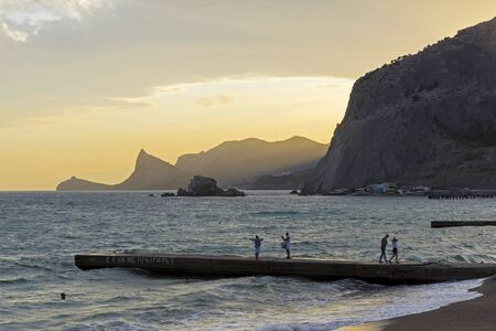Sunset in the bay of the resort town of Sudak.People walk along the breakwater. Crimea.