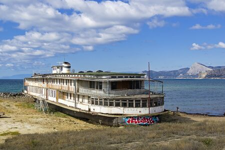 An old abandoned river boat stands on the ground near the sea. Kapsel bay, Crimea. Sunny day in September.