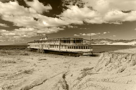 An old abandoned river boat stands on the ground near the sea. Kapsel bay, Crimea. Sunny day in September. Black and white version, sepia.