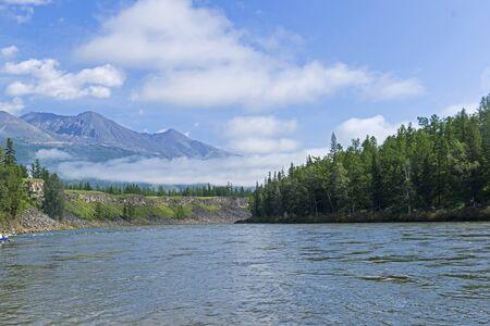 Beautiful layered clouds on a background of mountains. View from the banks of the Oka Sayan River. East Sayan, Buryatia, Siberia, Russia. 版權商用圖片