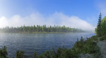 Panorama of the shore of a mountain river. Mountains are hidden by rising morning fog. The Oka Sayan river, Orkho-Bom gorge, East Sayan, Buryatia, Siberia, Russia.