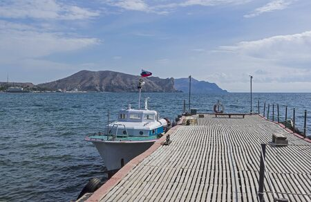A small boat is moored at the pier. The bay of the resort town of Sudak, Crimea. Sunny day in September.