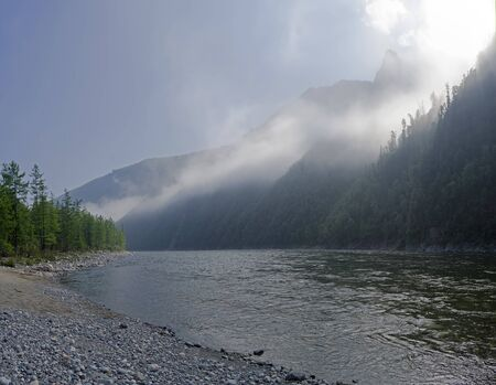 Morning on the mountain river. Rising night fog turns into light cloud cover. The Oka Sayan River in the Orkho-Bom Gorge. East Sayan, Buryatia, Siberia, Russia.