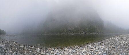 Foggy morning on the shore of a mountain river. The Oka Sayan River, East Sayan, Buryatia, Siberia, Russia.