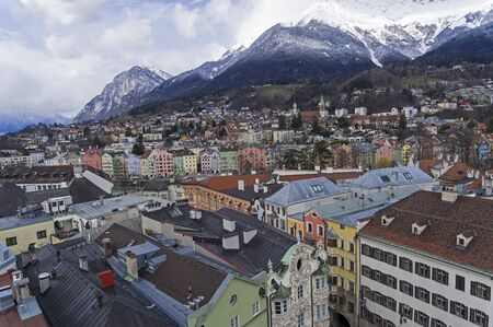 View from the top of the old clock tower to the historical center of Innsbruck and surrounding mountains. Austria.