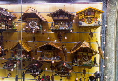 Innsbruck, Austria - March 3, 2020: The wall at the gift shop full of the clocks made in the national Tyrol style. Innsbruck, Tyrol, Austria.