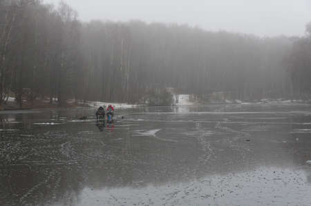 Two fishermen on the ice of a recently frozen pond. Overcast, fog, end of November. Landscape reserve