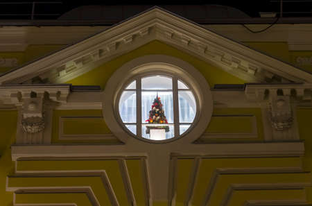 Christmas tree in a round window on the top floor of the house under the pediment. Evening, view from the street. Moscow, Russia.