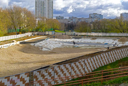 Reconstruction of Small Konkovsky pond, South-Western District of Moscow. Workers cover the waterproofing material placed on the bottom of the pond with gravel.