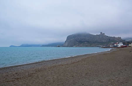 Empty beach in the bay of the resort town of Sudak, Crimea. Off-season. Cloudy day at the end of April.