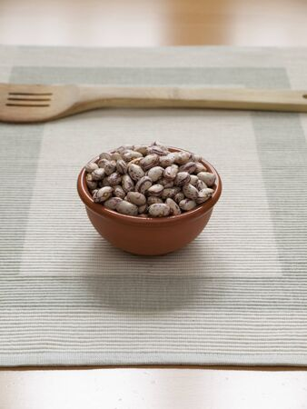 Close up view of organic Pinto beans in a bowl with a wodden Spoon Stock Photo