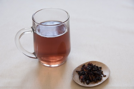 Dried Herbs and Fruits Preaparation in a bowl and Herbal Tea in a cup.