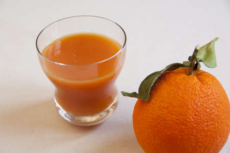 Close-up view of organic italian orange juice in a glass with one orange